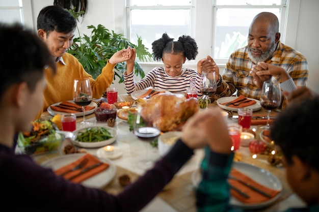 Family praying together before the thanksgiving day dinner