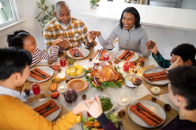 Семья молится вместе перед ужином в день благодарения