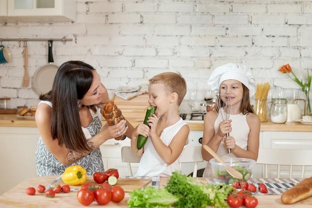 家族は台所で昼食を準備します。ママは娘と息子に新鮮な野菜のサラダを作るように教えます。健康的な自然食品、子供のためのビタミン