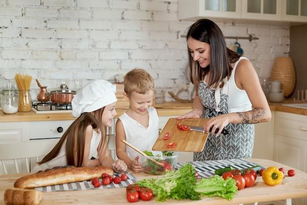 가족은 부엌에서 점심을 준비합니다. 엄마는 딸과 아들에게 신선한 야채 샐러드를 준비하도록 가르칩니다. 건강한 자연 식품, 어린 이용 비타민