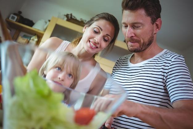 Family preparing salad in the kitchen