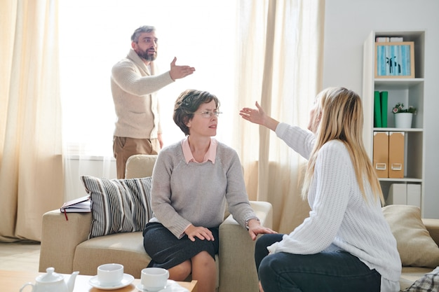 Family psychologist listening to quarrel of couple