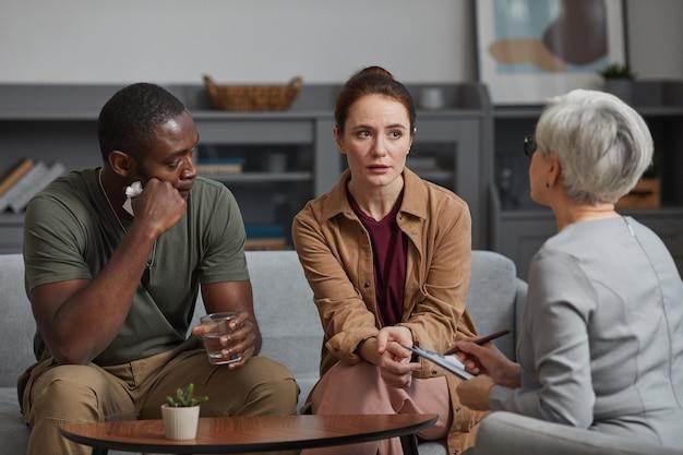 家族心理学者は、オフィスでの訪問中に若いカップルと一緒に働いています