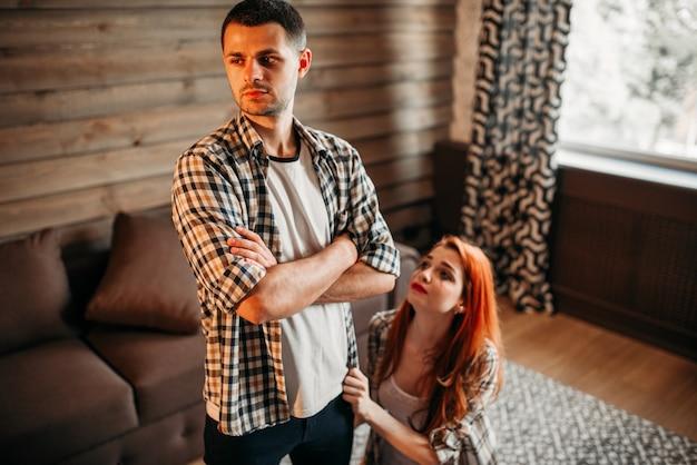家族の喧嘩、夫と妻の対立、ひざまずいた女性は謝罪します。問題の関係、ストレスのカップル