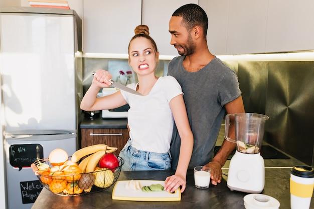 Семейная ссора на кухне. девушка с сердитым лицом с ножом и удивленный парень. спор мужа и жены, недопонимание, разрыв отношений, раздраженное лицо, имитация ссоры.