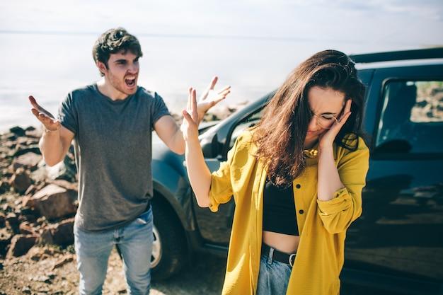 車の近くで家族の喧嘩。スキャンダルと不一致の概念。家族の危機。夫は妻に悲鳴を上げます。カップルは離婚を望んでいます。