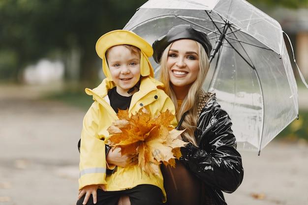 Famiglia in un parco piovoso. ragazzo con un impermeabile giallo e una donna con un cappotto nero.