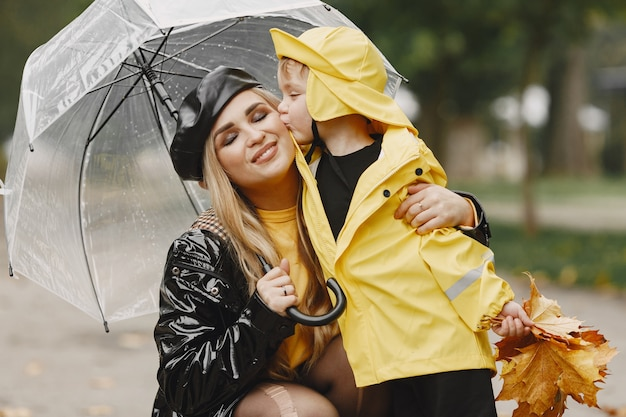 Family in a rainy park. kid in a yellow raincoats and woman in a black coat.