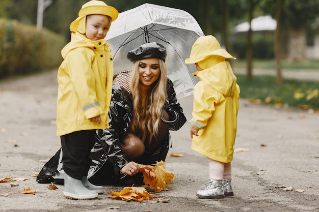 Family in a rainy park. kids in a yellow raincoats and woman in a black coat.