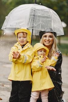 Famiglia in un parco piovoso. ragazzi con un impermeabile giallo e una donna con un cappotto nero.