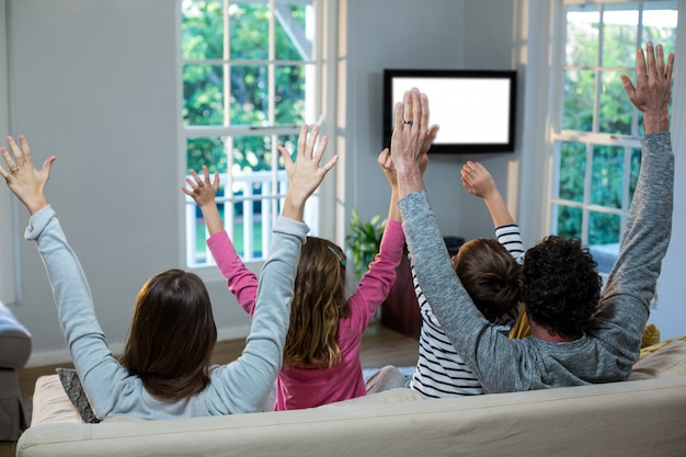 Family raising hands while watching television