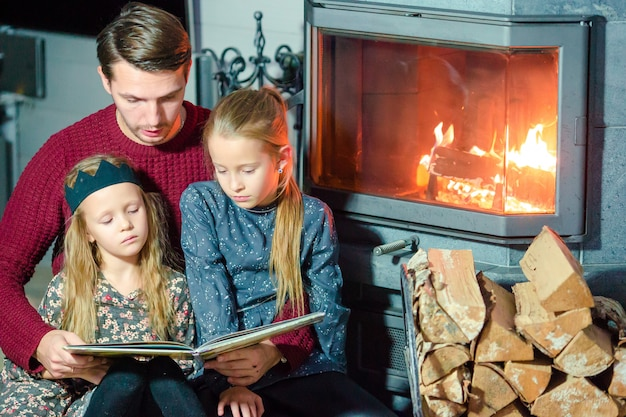 Family reading a book together near fireplace on christmas eve