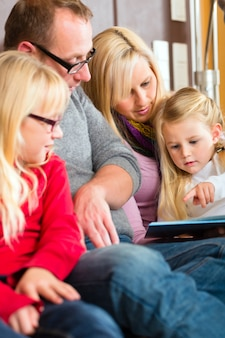 Family reading story in book on sofa in home