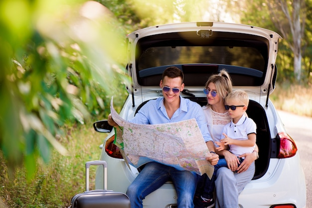 Family ready to travel and choose a place on the map where to go