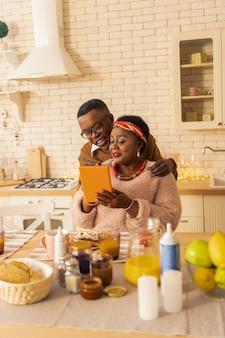 가족 관계. 태블릿 화면을 보면서 그의 여동생 뒤에 서있는 좋은 즐거운 남자