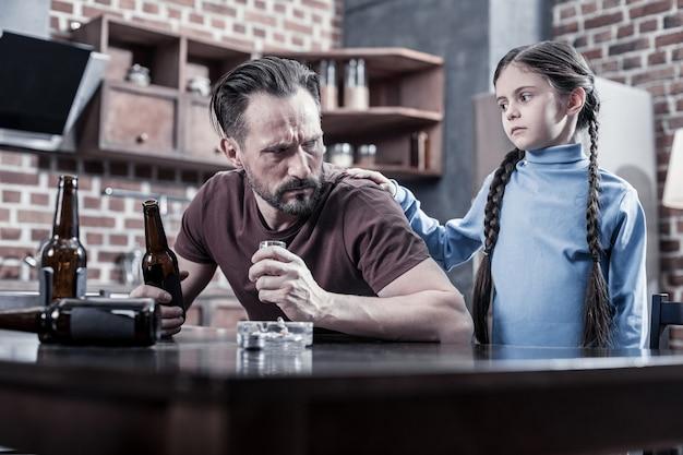 Семейные отношения. милая грустная мрачная девушка смотрит на своего отца и кладет руку ему на плечо, чувствуя грусть