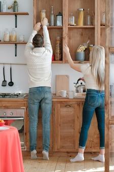 가족 관계. 현대 부엌에서 함께 요리하는 커플. 그의 아내가 상단 선반에 스파게티에 도달하도록 돕는 남자.