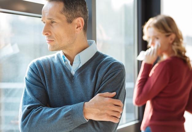 家族関係。家族で問題を抱えている間、窓を見て、彼の妻について考えている陽気で不幸なハンサムな男