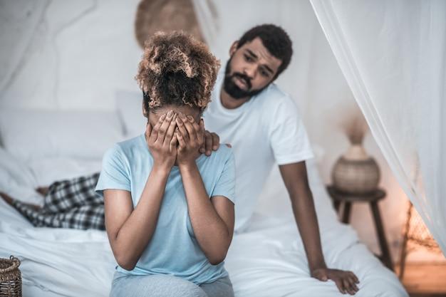 家族関係。手で顔を覆っている家庭服を着た浅黒い肌の女性と彼女の肩に触れているひげを生やした男
