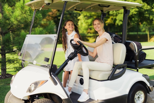 Family relationships golfers drive golf cart.
