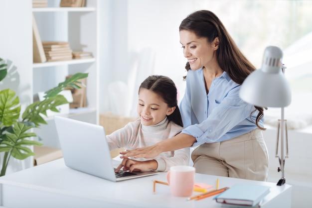 家族関係。彼女の娘の後ろに座って、ラップトップを使用するように彼女に教えながら笑っている素敵なポジティブな幸せな女性