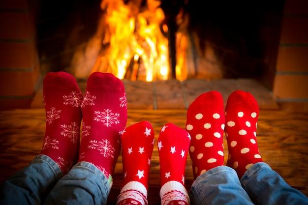 집에서 휴식하는 가족. 벽난로 근처에 크리스마스 양말에 발. 겨울 휴가 개념