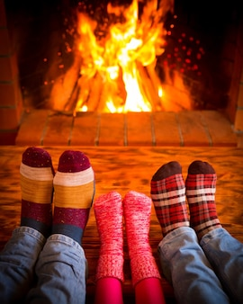 家族は家でリラックス。暖炉のそばのクリスマスソックスの足。冬の休日のコンセプト