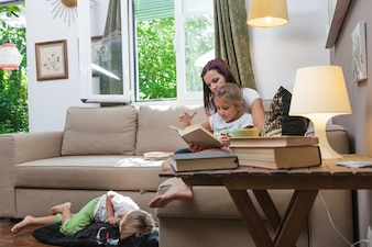 Family relaxing together reading in room