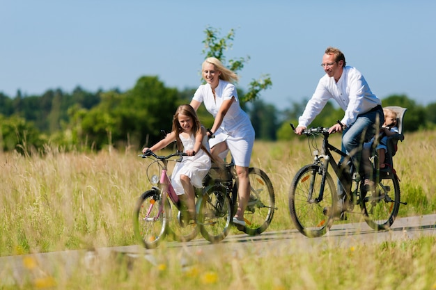 Family riding bikes in the country in summer