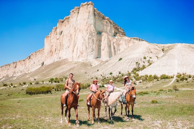 Family riding horses on rocks and mountains
