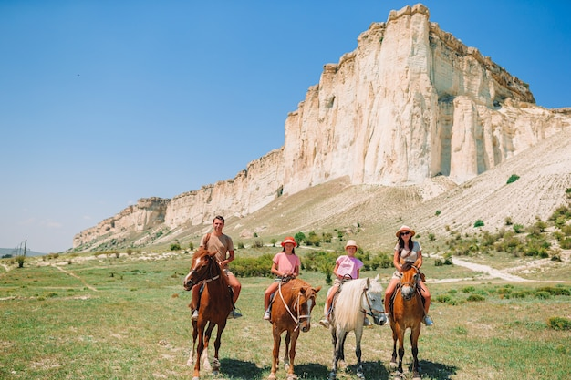 Family riding horses over rocks and mountains