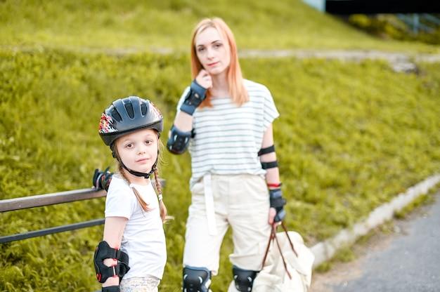 公園で家族のローラースケート。アクティブウォーク。母親と活発な散歩をしている就学前の女の子
