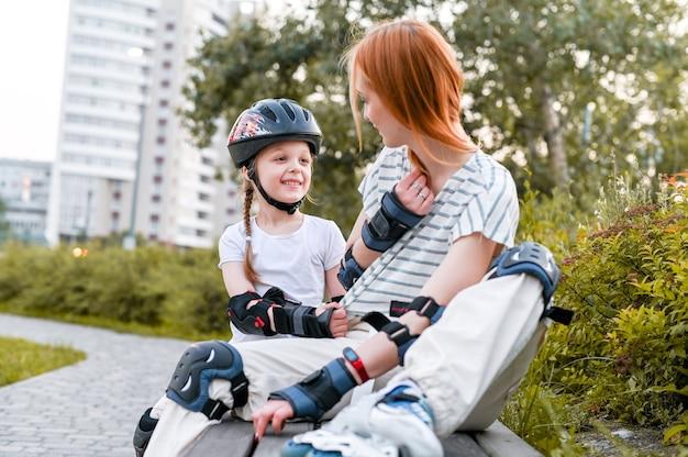 街の通りで家族のローラースケート。母親と活発な散歩をしている就学前の女の子