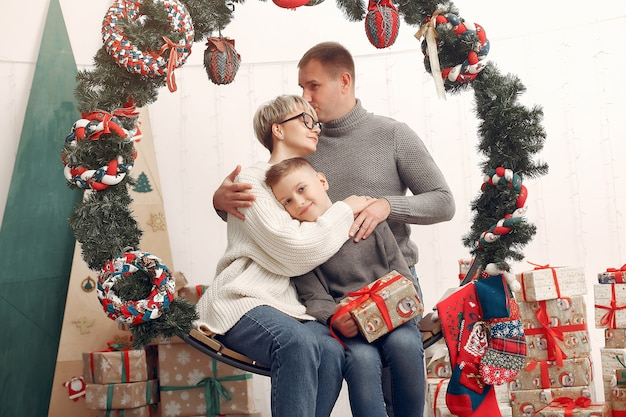 Family in a room. little boy near christmas decoration. mother with father with son