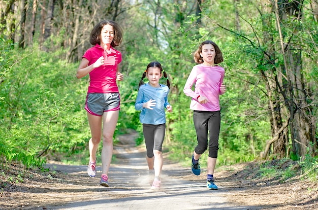 행복한 활동적인 어머니를 달리는 가족과 야외에서 조깅하는 아이들은 숲에서 아이들과 함께 달린다