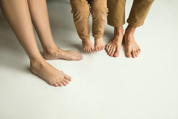 Le gambe della famiglia su bianco