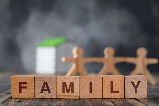 Family safety concept with wooden figures of people, cubes, model house side view.