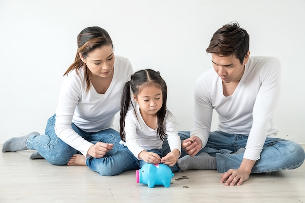 Family saving money putting coins into pig bank
