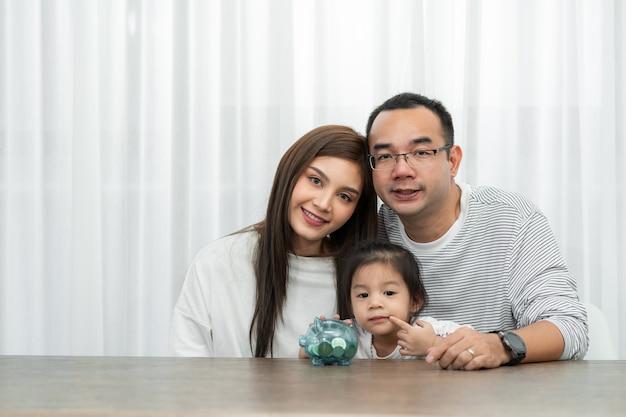 가족 저축, 예산 계획, 어린이 용돈. 멀리 아시아 가족 어머니와 딸이 돼지 저금통을 보여줍니다.