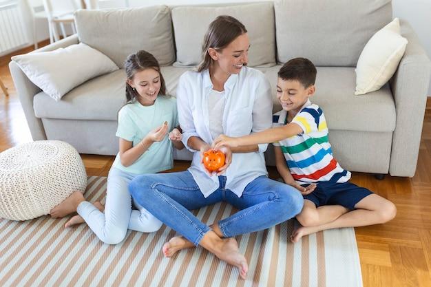 家族の節約。子供の予算計画、子供のポケットマネーを持つ若い母親。貯金箱のある家族。