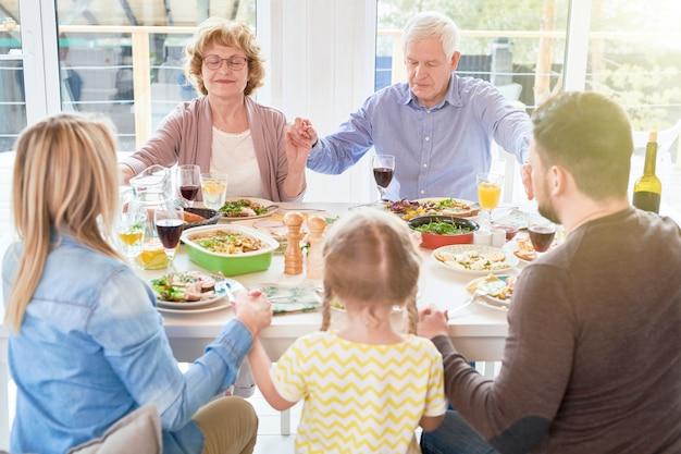 Family saying grace at dinner