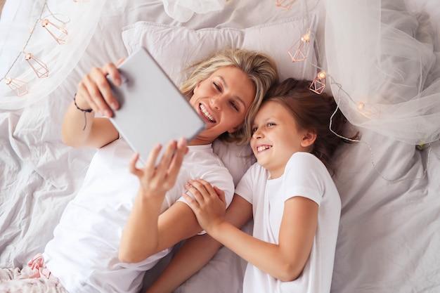 가족 장면. 행복 한 엄마와 딸이 침대에서