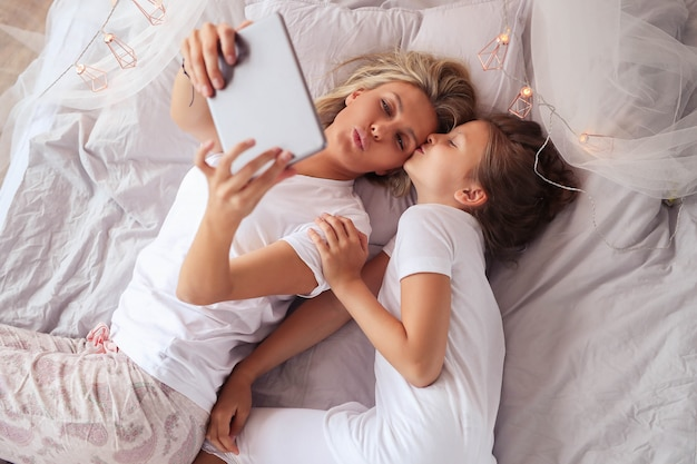 Семейная сцена. счастливая мать и дочь в постели
