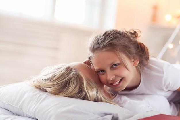 家族のシーン。ベッドで幸せな母と娘