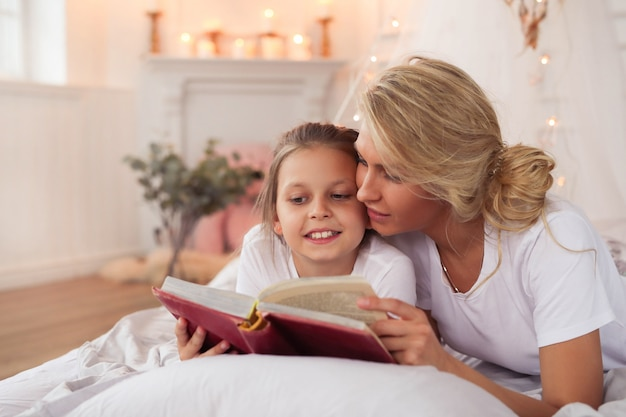 Family scene. happy mother and daughter in a bed