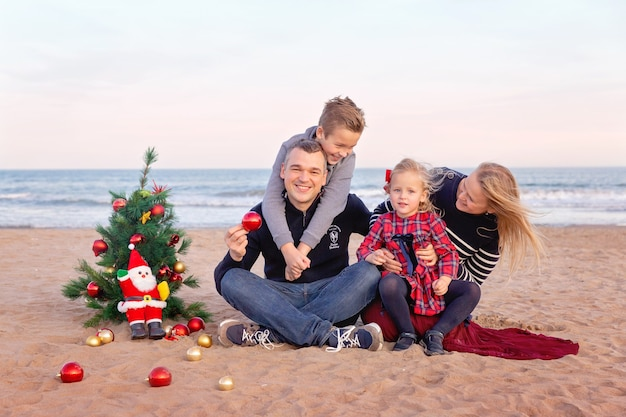Family at the seaside with christmas tree. happy parents with son and little daughter