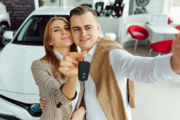 대리점에서 가족 셀카. 행복한 젊은 부부는 가족을 위해 새 차를 선택하고 구입합니다.