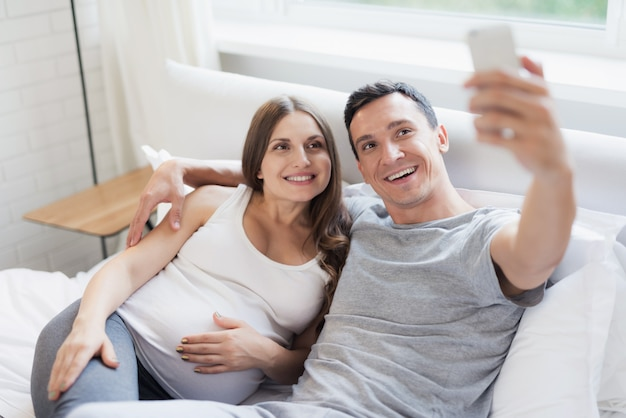 Семейная селфи на смартфоне. парень обнимает беременную.