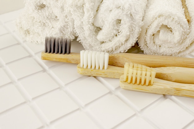 Family set of tree wooden bamboo toothbrushes with white towels on white tile bathroom . eco friendly concept. close up. selective focus. copy space