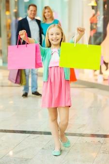 家族で買い物。小さな女の子が買い物袋を見せて笑っている間、ショッピングモールで陽気な家族の買い物